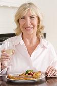 женщины, наслаждаясь едой, еды с бокалом вина — Стоковое фото
