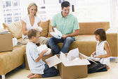 Family unpacking boxes in new home smiling — Stock Photo