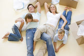 Family lying on floor by open boxes in new home smiling — Stock fotografie