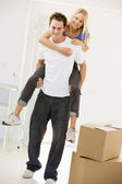 Husband giving wife piggyback in new home smiling — Stock Photo