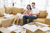 Couple relaxing with coffee by boxes in new home smiling — Stock Photo