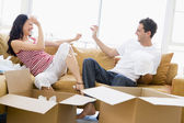 Couple playfully unpacking boxes in new home smiling — Stock Photo
