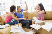Three girl friends playfully unpacking boxes in new home smiling — Stock Photo