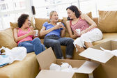 Three girl friends relaxing with coffee by boxes in new home smi — Stock Photo
