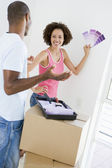 Couple with paint swatches in new home smiling — Stock Photo
