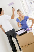 Couple painting room in new home smiling — Stock Photo