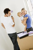 Family painting room in new home smiling — Stock Photo