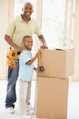 Father wearing tool belt standing by son and boxes in new home s — Stock Photo
