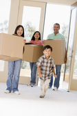Family with boxes moving into new home smiling — Stock Photo