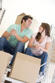 Couple sitting on staircase with boxes in new home smiling — Stock Photo