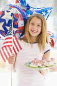 Young girl outdoors on fourth of July with flag and cookies smil — 图库照片