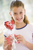 Young girl on Valentine's Day holding love themed balloon smilin — Stock Photo