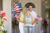 Family at front door on fourth of July with flags and cookies sm — Foto de Stock
