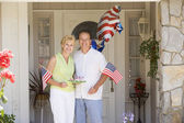 Couple at front door on fourth of July with flags and cookies sm — Stockfoto