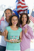 Family outdoors on fourth of July with flags and cookies smiling — Stok fotoğraf