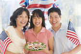 Family outdoors on fourth of July with flags and cookies smiling — Zdjęcie stockowe