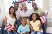 Family in living room on fourth of July with flags and cookies s — Stok fotoğraf