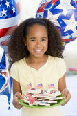 Young girl on fourth of July with balloons and cookies smiling — Stok fotoğraf