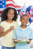 Brother and sister on fourth of July with flag and cookies smili — ストック写真