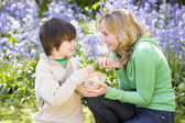 Mother and son on Easter looking for eggs outdoors smiling — Stock Photo