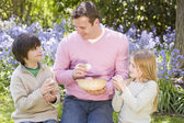 Father and two young children on Easter looking for eggs outdoor — Stock Photo