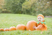 Baby boy outdoors in pumpkin costume with real pumpkins — Zdjęcie stockowe