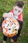 Young boy outdoors wearing vampire costume on Halloween holding — Stockfoto