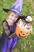 Young girl outdoors in witch costume on Halloween holding candy — Stockfoto