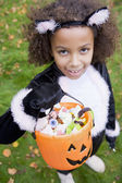 Young girl outdoors in cat costume on Halloween holding candy — ストック写真