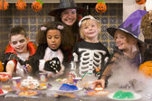 Four young friends and a woman at Halloween eating treats and sm — Photo