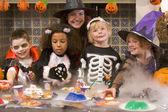 Quatro jovens amigos e uma mulher no dia das bruxas, comendo doces e sm — Foto Stock
