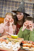 Mother and two children at Halloween playing with treats and smi — Stok fotoğraf