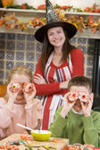 Mother and two children at Halloween playing with treats and smi — ストック写真
