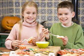 Brother and sister at Halloween making treats and smiling — Foto Stock