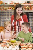 Mother and two children at Halloween making treats and smiling — Stockfoto