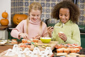 Two young girl friends at Halloween making treats and smiling — Stock Photo
