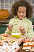 Young girl at Halloween making treats and smiling — Stok fotoğraf
