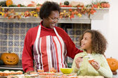 Grandmother and granddaughter making Halloween treats and smilin — ストック写真