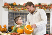Father and son carving jack o lanterns on Halloween and smiling — Zdjęcie stockowe