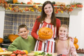 Mother and two children carving jack o lanterns on Halloween and — Stockfoto