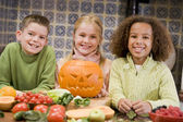 Three young friends on Halloween with jack o lantern and food sm — Stok fotoğraf