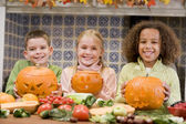 Three young friends on Halloween with jack o lanterns and food s — Stok fotoğraf