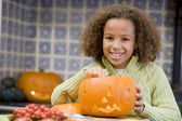 Young girl on Halloween with jack o lantern smiling — Stock fotografie