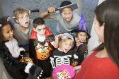 Sechs kinder in kostümen trick oder behandlung im haus der frau — Stockfoto