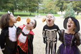 Four young friends on Halloween in costumes eating donuts hangin — Zdjęcie stockowe