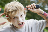 Young boy with scary Halloween make up and plastic knife through — Zdjęcie stockowe