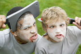 Two young boys with scary Halloween make up and plastic knives t — Zdjęcie stockowe