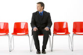 Businessman Sitting In Row Of Empty Chairs — Stock Photo