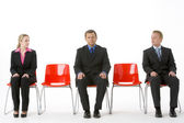 Three Business Sitting On Red Plastic Seats — Stock Photo