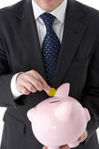 Businessman Putting Coin Into Piggy Bank — Stockfoto